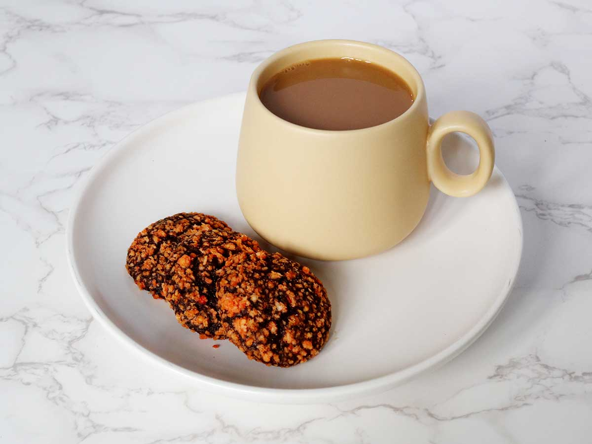 Nordic-style yellow coffee mug on white plate with three pieces of choco butternut cookies