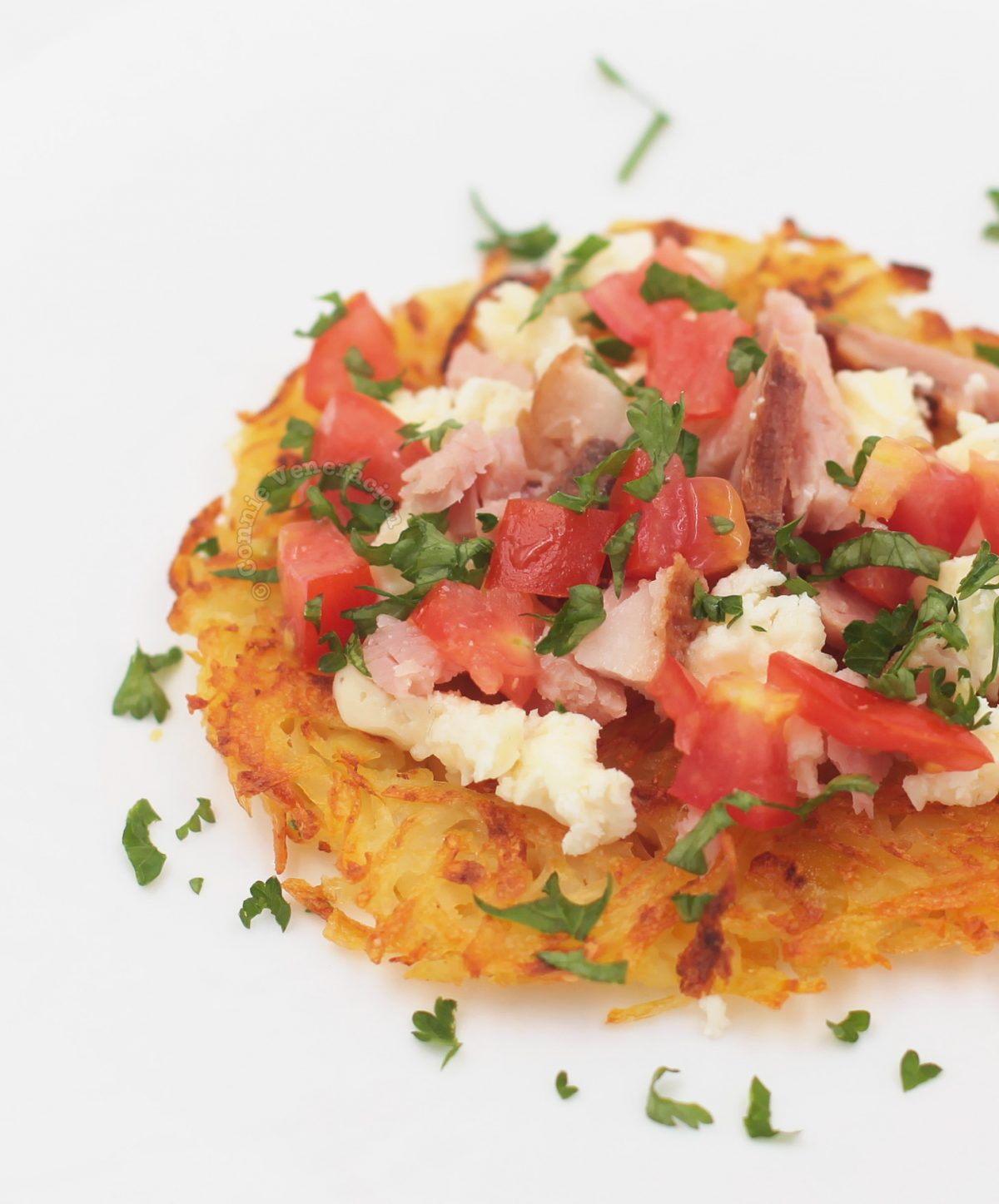 Crumbled feta, chopped smoky ham and juicy tomatoes on top of rösti (Swiss fried grated potatoes)