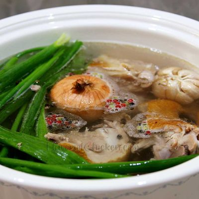 Chicken soup bones with herbs and spices in pot
