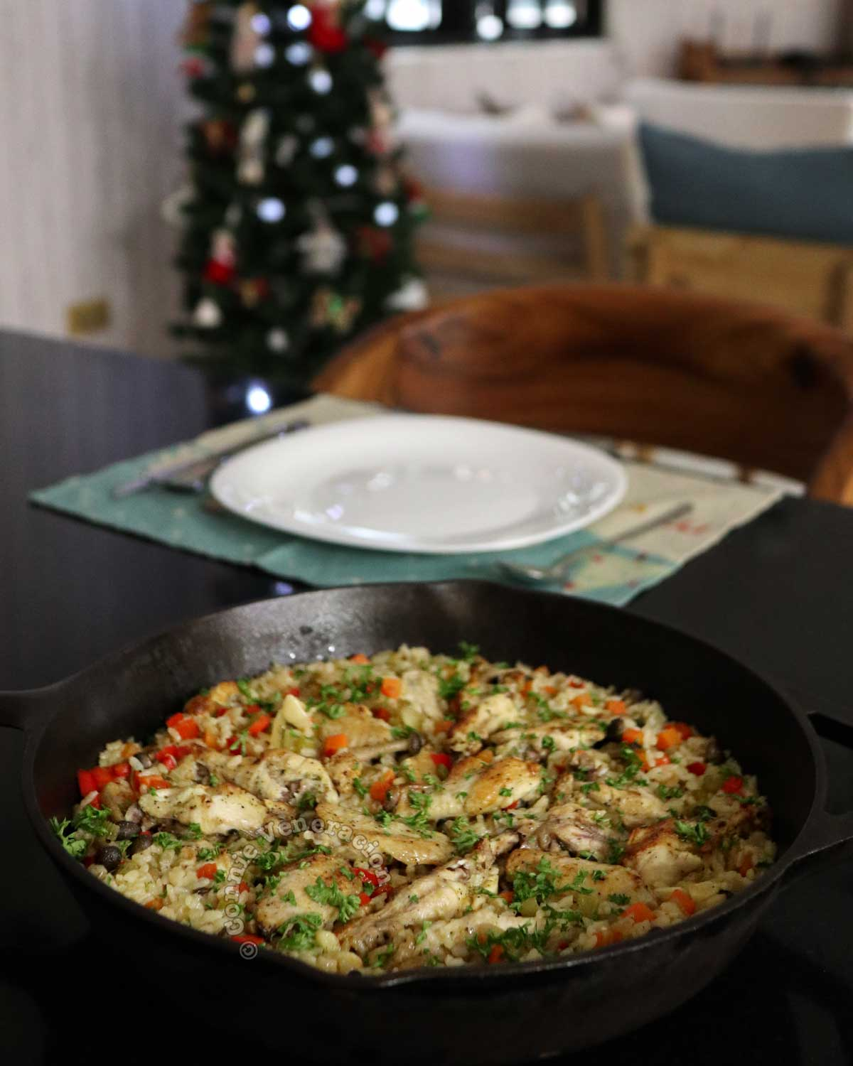 Chicken and mushrooms rice casserole on dining table with Christmas tree in background