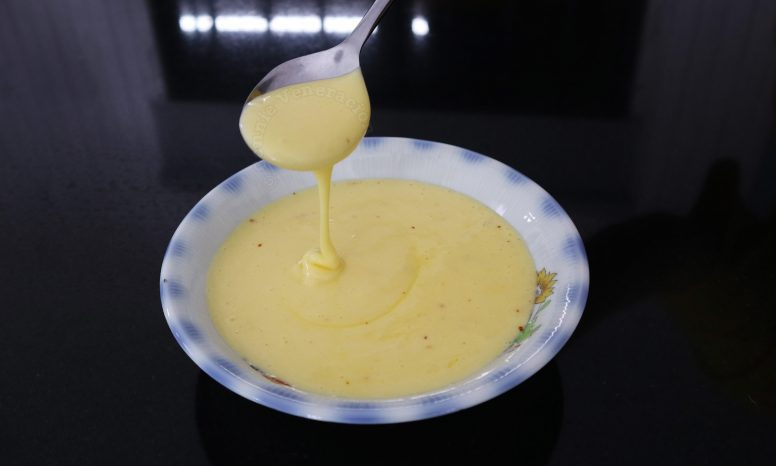 Hollandaise sauce, in ribbon stage, falling from a spoon