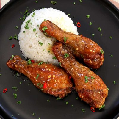 Spicy honey mustard fried chicken with white rice in black plate