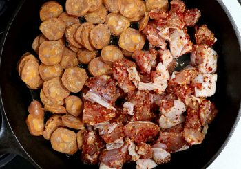 Browning Andouille sausages and chicken in a cast iron pab