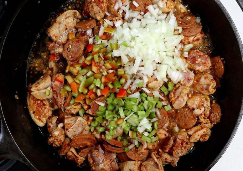Adding onion, celery and bell pepper to browned Andouille and chicken