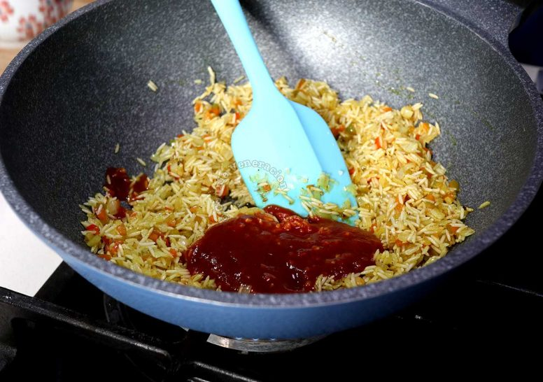 Adding tomato sauce to rice