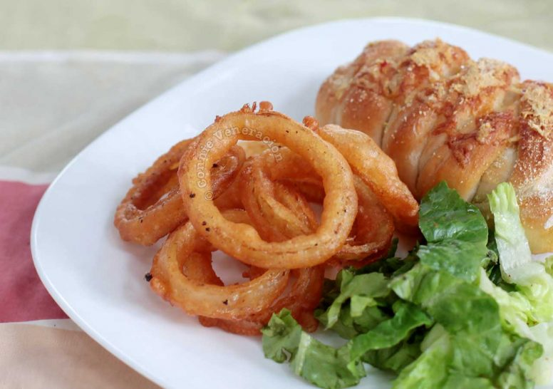 A side dish of spicy onion rings, bread and lettuce