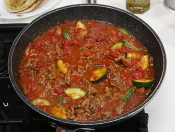 Cooking meat and vegetables for shakshuka
