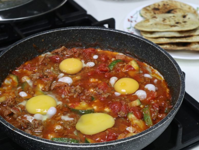 Cracking eggs into meat and vegetable stew in pan to make shakshuka