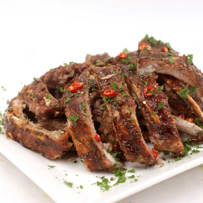 Cajun Pork Spare Ribs on Serving Plate Garnished with Sliced Chilies and Chopped Parsley