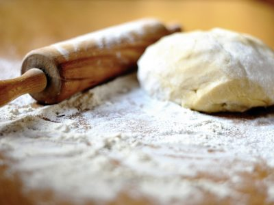 Bread dough and rolling pin on floured work surface