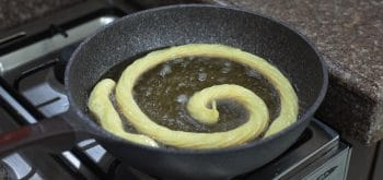 Frying piped choux pastry in hot oil to make churros