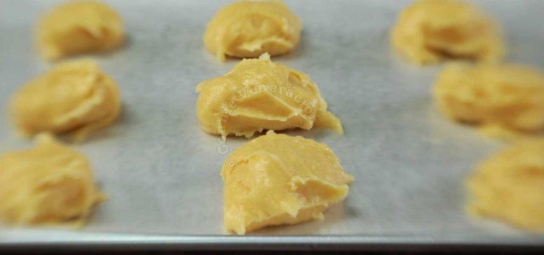 Adding eggs to butter and flour to make choux pastry (pâte à choux) piped on baking tray
