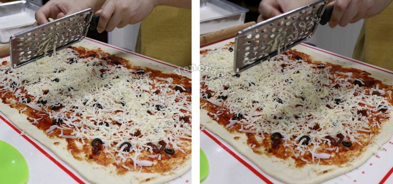 Grating cheese on rolled dough