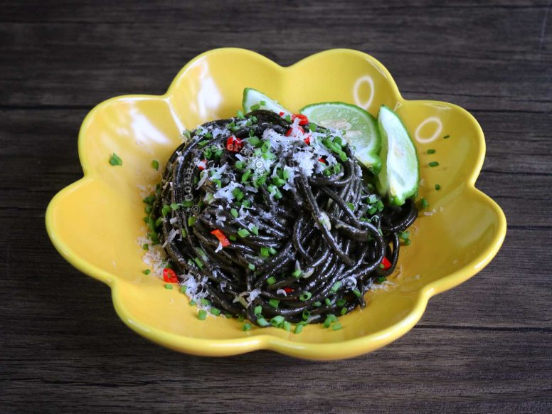 Squid Ink Pasta Aglio e Olio Garnished with Chilies, Scallions, Shaved Pecorino and Served with Lime Wedges on the Side