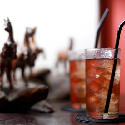 Tequila Cranberry Cocktail in Tumblers (Hard carved wooden horses in background)