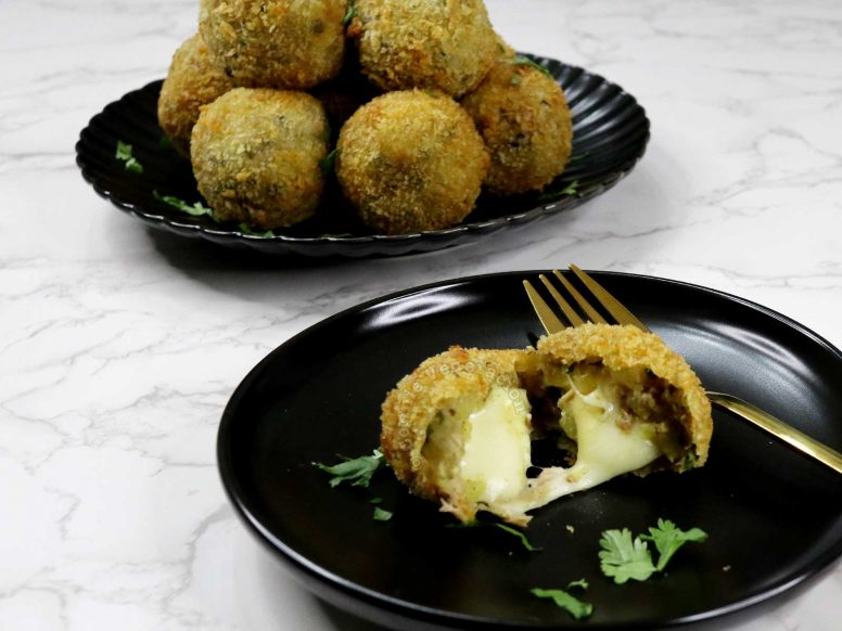 cheese-stuffed potato balls showing center with gooey cheese