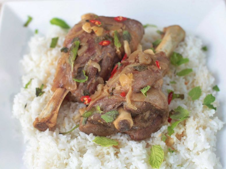 Braised Lamb Shanks Garnished with Mint Leaves, Sliced Chilies and Served Over Rice