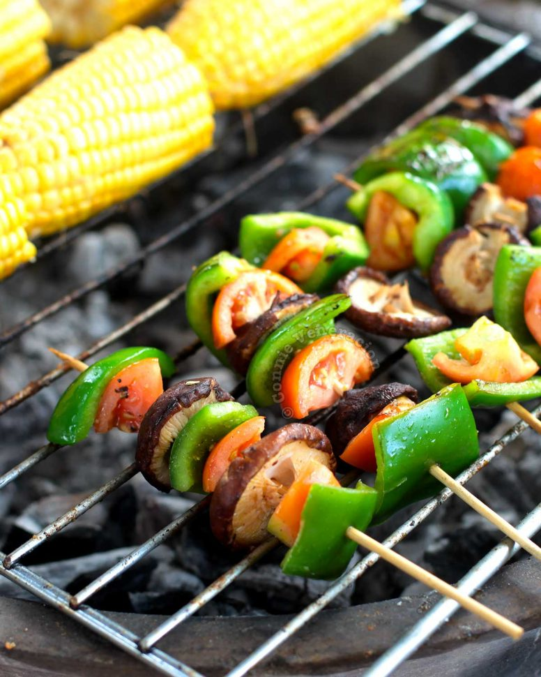Skewered shiitake, bell peppers and tomatoes grilling over hot charcoal