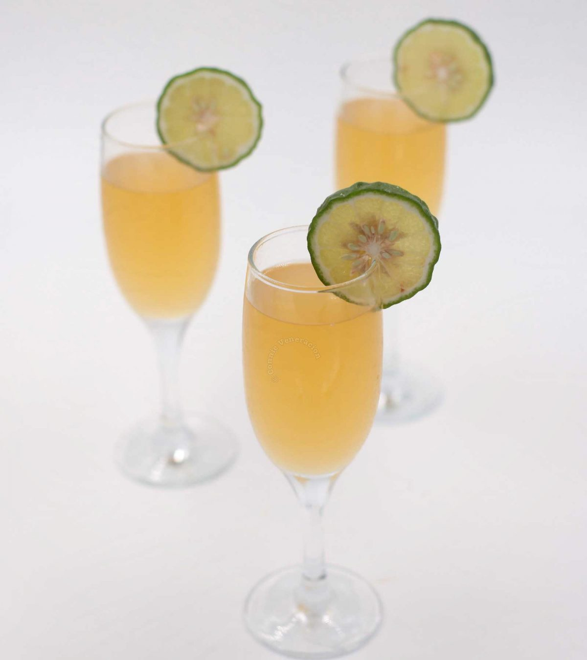 Three glasses of Lime Juice Mimosa garnished with kaffir lime slices