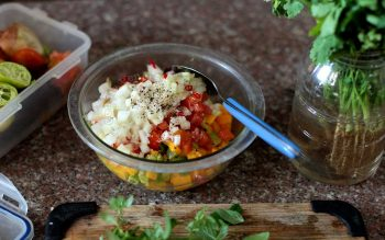 Tossing onions, tomatoes, mango and avocado in a bowl