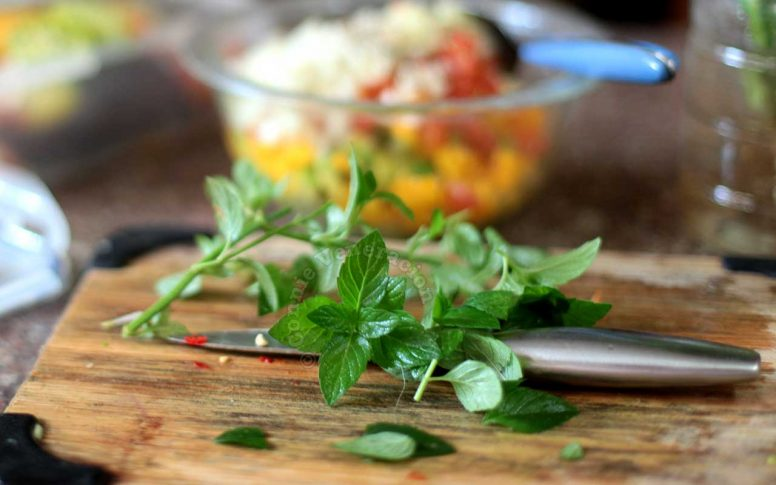 Fresh mint and basil on a bamboo chopping board