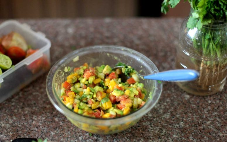 Adding chopped basil and mint to mango and avocado salsa