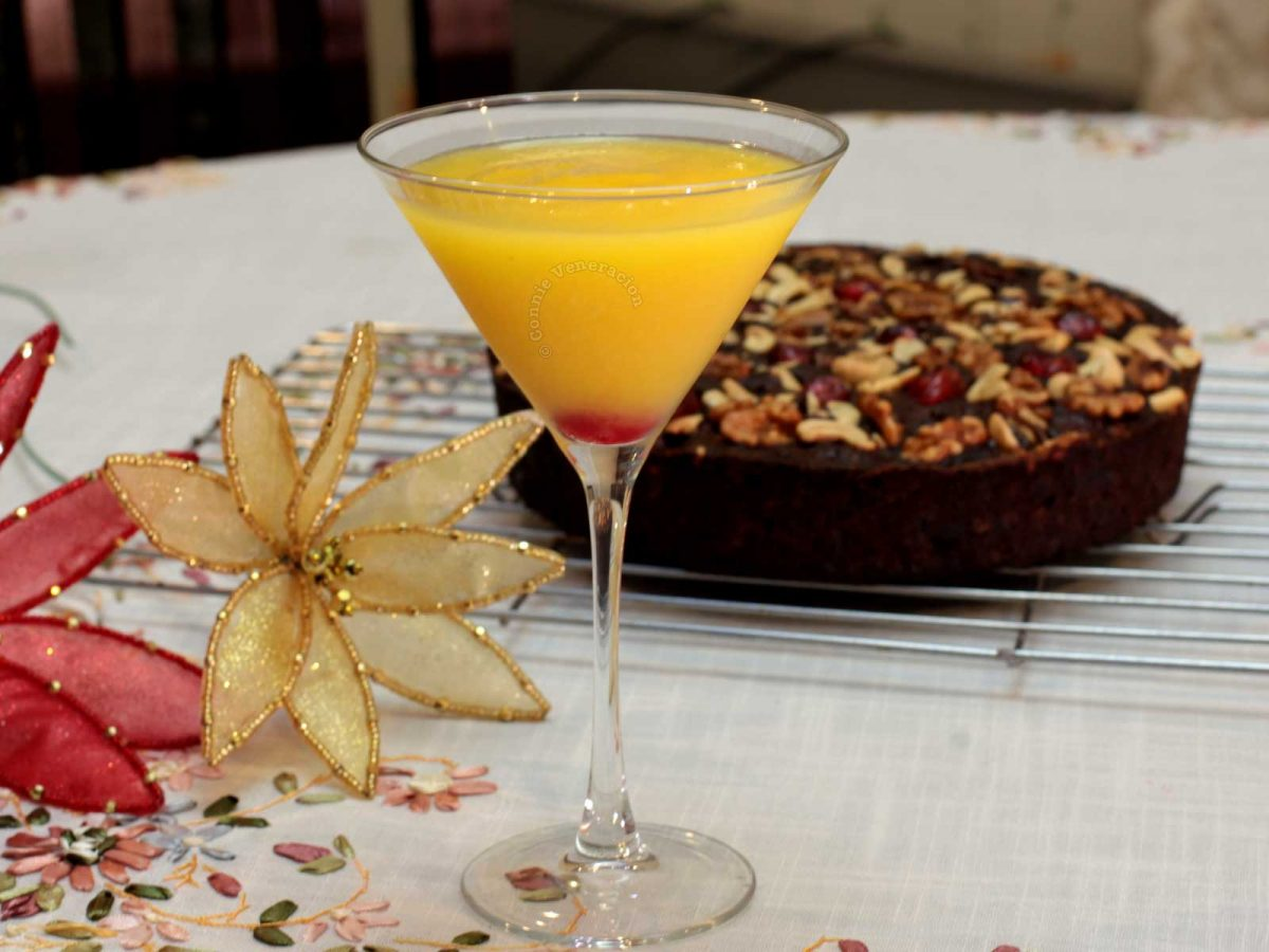 Mango Vodka Cocktail with Fruit cake and Christmas ornaments in the background