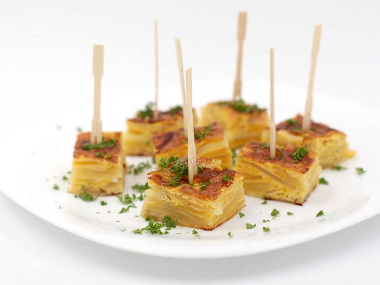 Spanish torta served skewered and sprinkled with parsley