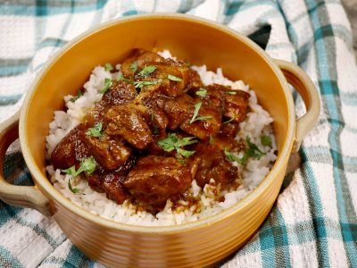 Mexican pork adobada served over rice in yellow bowl