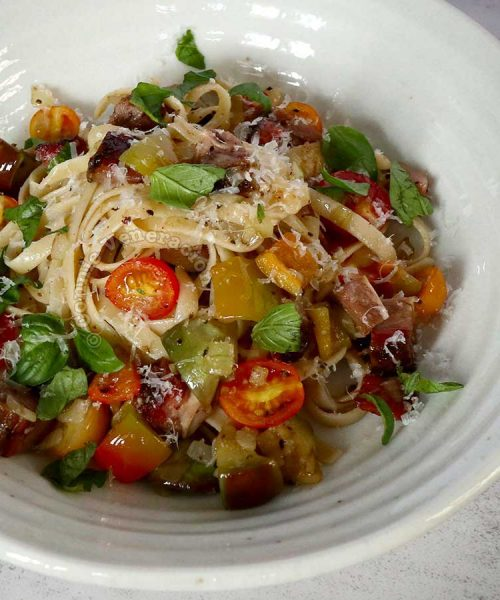Beef brisket bbq pasta topped with fresh basil and grated Pecorino