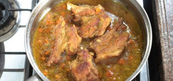 Browned pork ribs in pan with beer and vegetables