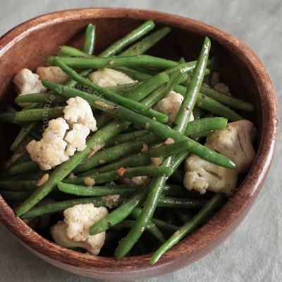 Green Beans and Cauliflower With Herb and Spice Butter in a Wooden Bowl