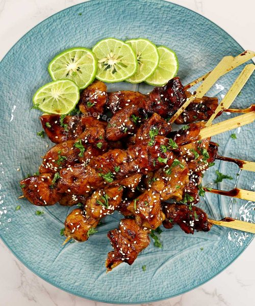 Honey balsamic chicken skewers sprinkled with parsley and toasted sesame seeds, and served with lime slices on the side