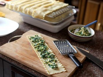 Spreading spinach and cheese on lasagna