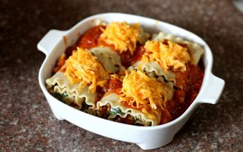 Lasagna roll-ups smothered with shredded cheese