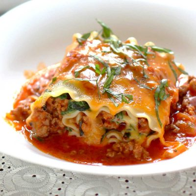 Meaty lasagna roll-up garnished with basil chiffonade