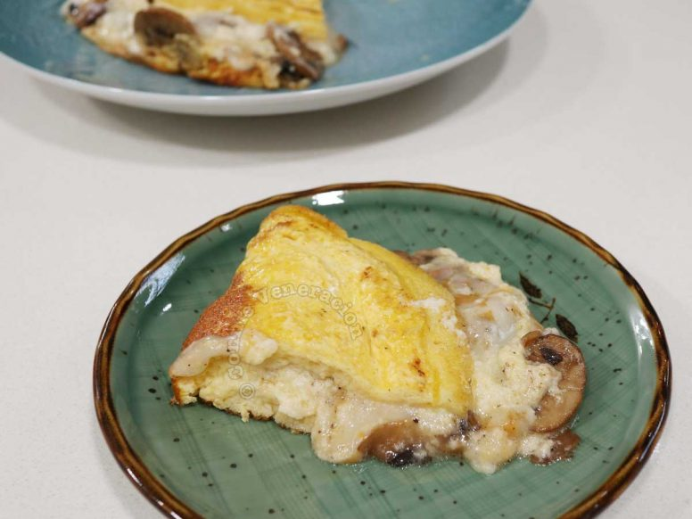 A portion of cheese and mushroom omelette on a green plate