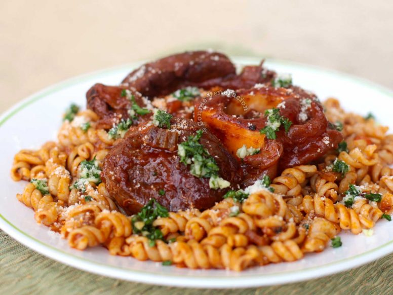 Osso buco served over pasta then sprinkled with gremolata