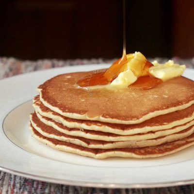 A stack of pancakes, made from scratch, topped with butter and drizzled with honey