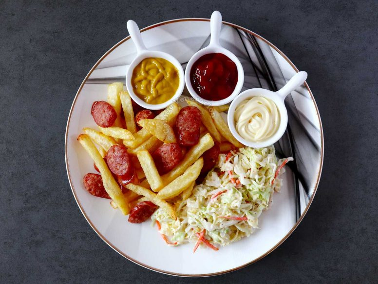 Salchipapas with mustard, ketchup and mayo, and coleslaw on the side