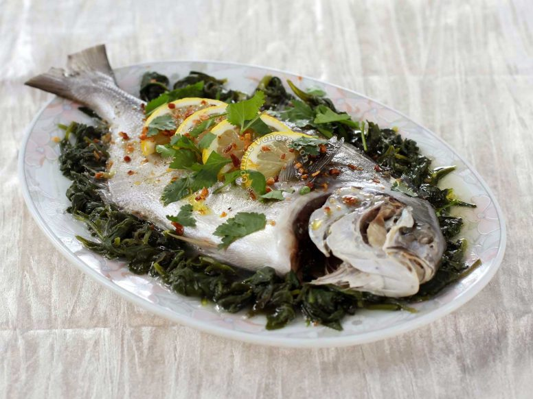 Steamed Whole Fish With Lemon and Olive Oil on a Bed of Spinach
