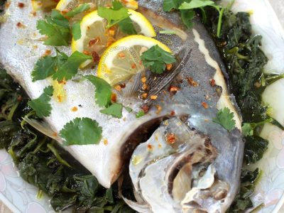Steamed Whole Fish With Lemon and Olive Oil Garnished with Lemon Slices, Fried Garlic and Cilantro