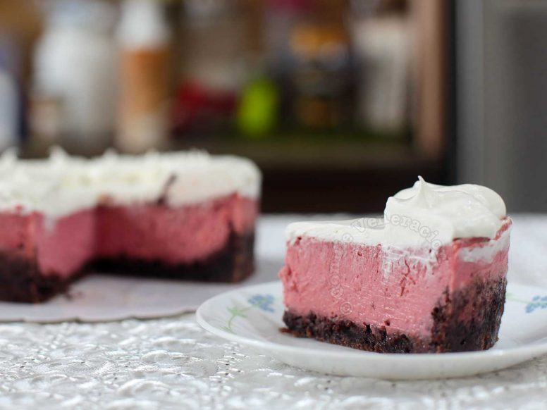 A Slice of Strawberry Cheesecake with Brownie Crust Topped with Whipped Cream