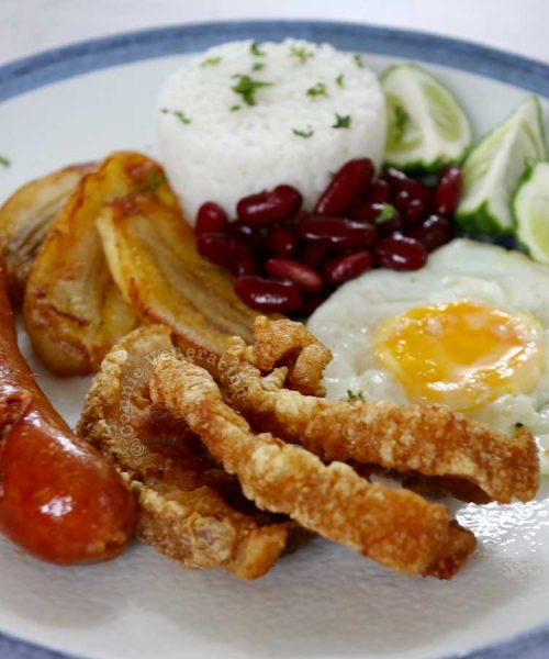 Chicharron (fried pork belly) served with sausage, egg, bananas, rice and beans