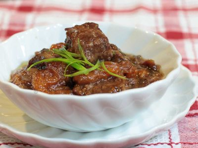 Beef and apricot stew in white bowl