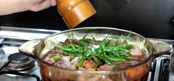 Sprigs of tarragon on top of beef and apricots in pot