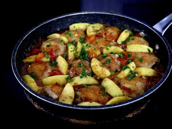 Chicken apple stew in pan sprinkled with parsley