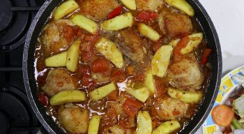 Stewing chicken, vegetables and apples in pan