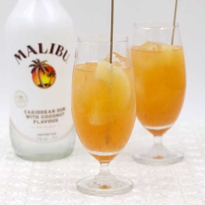 Pineapple, grapefruit and coconut rum cocktail garnished with skewered pineapple