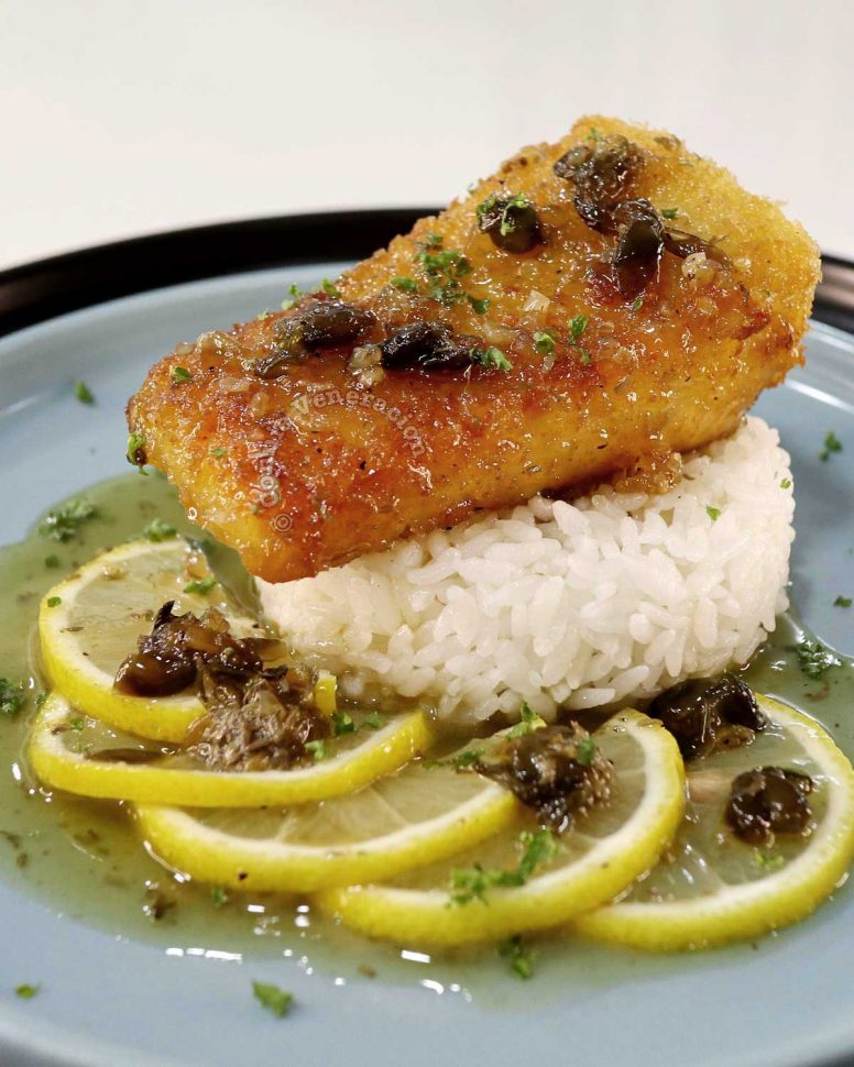 salmon piccata with rice, lemon slices and sauce
